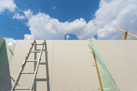 Construction new and modern modular house from composite sip panels. Low angle view photo of metal ladder standing by the wall against blue sky background Stockfoto