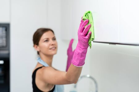 Selective focus of young adult housewife in apron and rubber gloves using wipe cloth and cleaning contemporary white kitchen cabinet at home