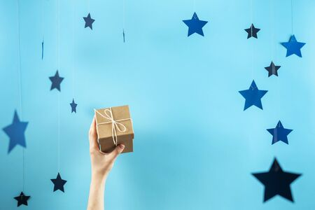 Happy anniversary! Photo of craft gift box with ribbon in woman hands isolated against pastel blue background with copy or empty space for text and paper stars decorations 스톡 콘텐츠