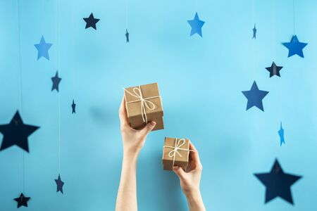 Christmas, hew year or birthday concept! Photo of two small and big wrapped gift box with ribbon in girls hands isolated against vivid blue background with stars decor