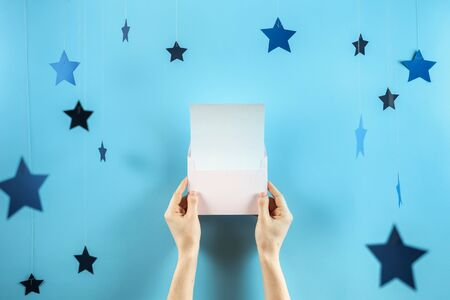 Party time concept! Inviting on event in female hands isolated against shine blue background with copy or empty space for text and paper stars decorations