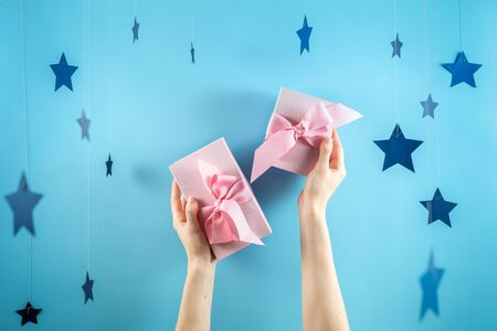 Happy birthday party! Two beautiful and pink wrapped gift box with ribbon in girls hands isolated against pastel blue background with paper stars decorations 스톡 콘텐츠
