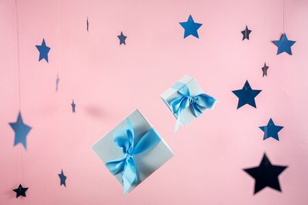 Party time concept! Two wrapped gift box with blue ribbon isolated against pastel pink background with paper stars decorations