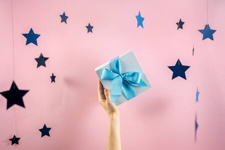 Christmas, hew year or birthday concept! Big blue wrapped gift box with ribbon in girls hands isolated against pink and bright background with beautiful stars decor