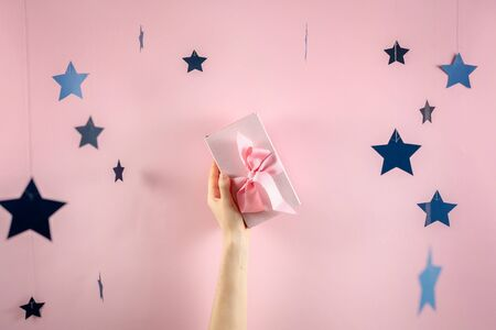 Happy birthday party! Pink and big wrapped gift box with ribbon in girls hands isolated against shine background with paper stars decorations 스톡 콘텐츠