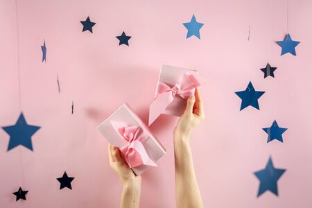 Easy shopping with sale and discount! Two pink wrapped gift box with ribbon and bow in female hands isolated against bright background with small blue stars decor 스톡 콘텐츠