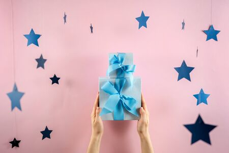 Happy holiday! Pile or stack of two wrapped gift box with ribbon in woman hands isolated against bright pastel pink background with stars decor 스톡 콘텐츠