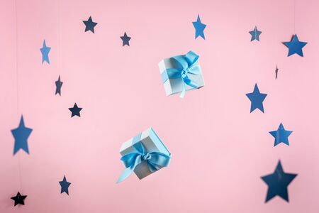 Happy anniversary! Two small and blue wrapped gift box with ribbon bow isolated against shine background with paper stars decorations 스톡 콘텐츠