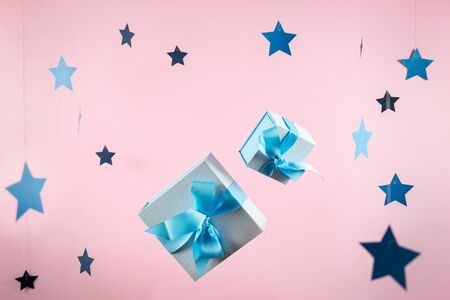 Christmas, hew year or birthday concept! Two small and big blue wrapped package or gift box with ribbon isolated against bright pink background with stars decor