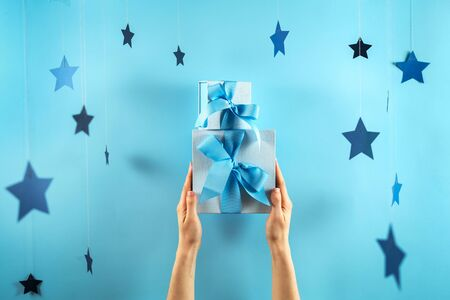 Happy holiday! Pile or stack of wrapped gift box with ribbon in woman hands isolated against vivid light blue background with handmade stars decor 스톡 콘텐츠