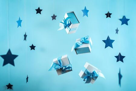 Happy anniversary! Group pf wrapped gift box or present with beautiful blue ribbon flying isolated against pastel background with paper stars decorations
