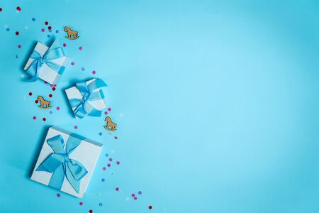 High angle above top view of wrapped gift box or presents with wooden horses toy isolated against shine background with copy or empty space for text with paper and colorful confetti