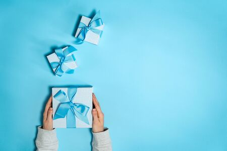 Happy holiday! Flat lay and high angle above top view of blue and big wrapped gift box with ribbon in woman hands isolated against vivid background with copy or empty space for text 스톡 콘텐츠