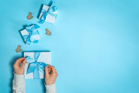Happy birthday party! Flat lay and top view of group of wrapped gift box with ribbon bow in girls hands isolated against shine blue background with copy or empty space for text and wooden horses toy