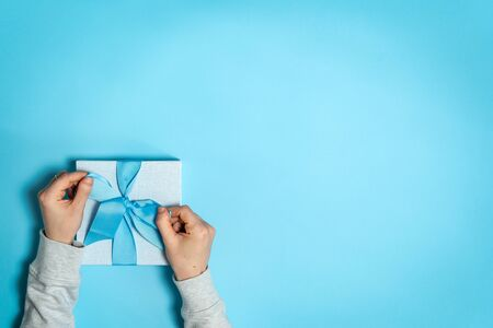 Easy shopping with sale and discount! Flat lay and high angle above top view of big blue wrapped gift box with bow in female hands isolated against bright background with copy or empty space for text