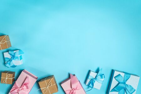 Happy holiday! Flat lay and high angle above top view group of wrapped blue and pink presents or gift box with beautiful bow isolated against bright background with copy or empty space for text