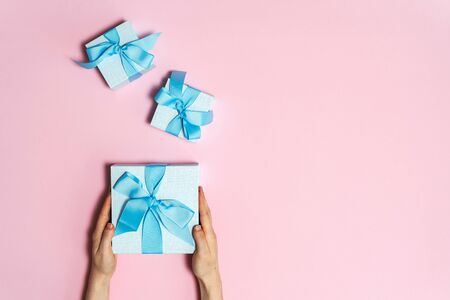 Christmas, hew year or birthday concept! Flat lay and high angle above top view of three blue and beautiful wrapped present in girls hands isolated on pink background with copy or empty space for text