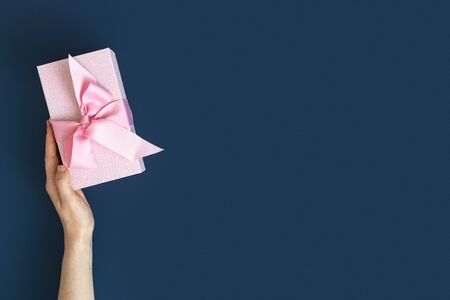 Party time concept! Flat lay and high angle above top view of pink wrapped present box with bow in female hands isolated against deep blue background with copy or empty space for text 스톡 콘텐츠
