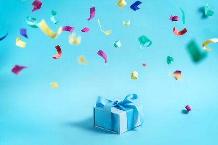 Happy holiday! Beautiful blue wrapped gift or present box with ribbon isolated against bright background with copy or empty space for text and paper and colorful confetti decorations