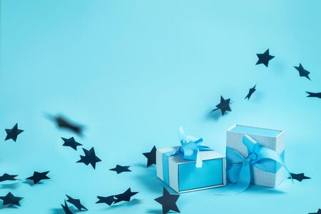 Happy birthday party! Two small and beautiful blue wrapped gift box isolated against pastel background with copy or empty space for text and paper stars decorations