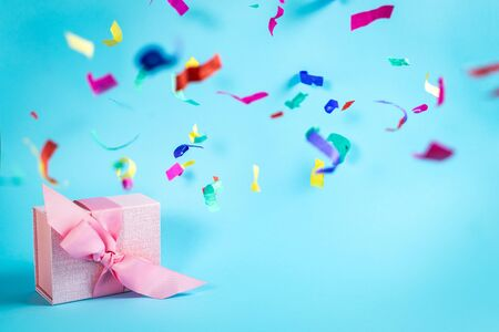 Easy shopping with sale and discount! Amazing and wonderful pink wrapped gift box with ribbon isolated against vivid blue background with copy or empty space for text and paper colorful confetti