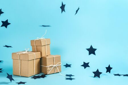 Happy anniversary! Craft present or gift box isolated against shine blue background with copy or empty space for text and flying paper stars decorations 스톡 콘텐츠