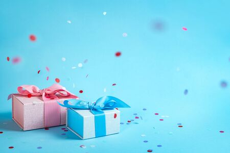 Party time concept! Two wonderful and lovely wrapped gift or present box with ribbon bow isolated against pastel blue background with copy or empty space for text and paper colorful confetti