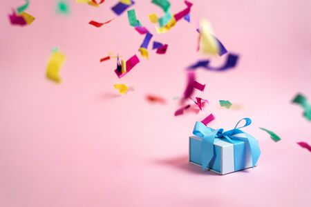 Easy shopping with sale and discount! Beautiful blue wrapped present or gift box isolated on background with copy or empty space for advertised text and paper colorful confetti decorations