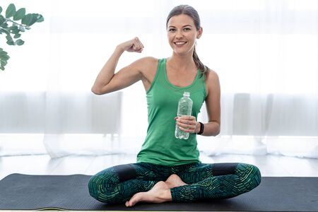 Happy young woman smiling, looking at camera, sitting on fitness mat, holding bottle with drink water and showing bicep muscle