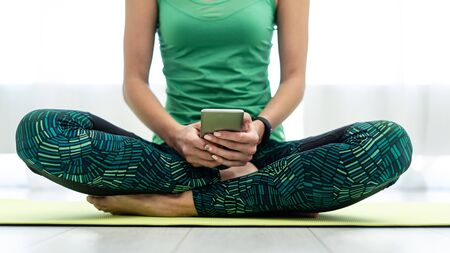 Cropped view of young adult woman sitting on fitness mat and holding online app in smartphone after training at home Imagens