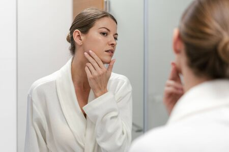 Young and gorgeous woman in white bathrobe standing in bright light bathroom with mirror. She looking at her reflection with calm face, holding hand on cheek, checking skin