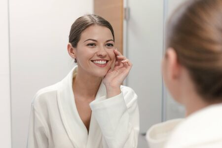 Young adult and charming woman in white bathrobe standing in bright light bathroom with mirror. She looking at her reflection, smiling wide and holding hand near face