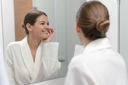 Young adult and charming woman in white bathrobe standing in bright light bathroom with mirror. She looking at her reflection, holding hand near face, checking skin and smiling wide