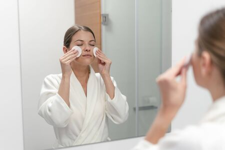 Woman with closed eyes in white bathrobe holding cotton pad in hands, looking at mirror in bathroom and remove make up from face