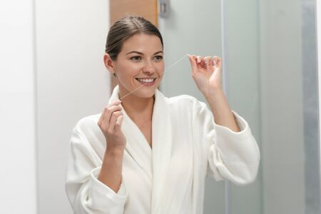 Young adult woman in white bathrobe holding dental floss in hands, looking at mirror, standing in bathroom and brushing teeth