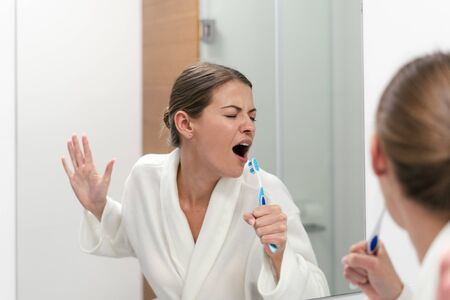 Funky young woman in white bathrobe standing in bathroom, holding tooth brush, looking at mirror and singing at toothbrush like in microphone