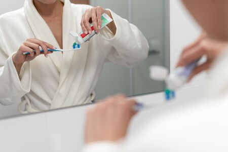 Cropped view of woman standing in bathroom, holding toothbrush, toothpaste and brushing teeth 写真素材