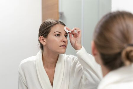 Young adult woman in white bathrobe holding cotton pad in hands, looking at mirror in bathroom and remove make up from face
