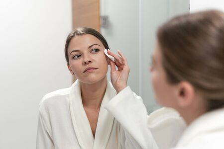 woman in white bathrobe holding cotton pad in hands, looking at mirror in bathroom and remove make up from face