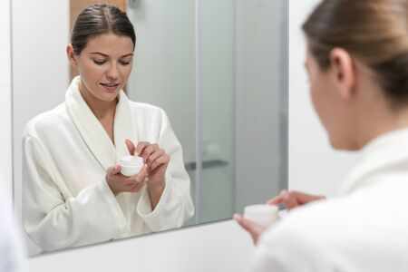 Attractive, young adult woman standing in bathroom near mirror, holding jar with moisturizer cream in hands and smiling nice Stok Fotoğraf