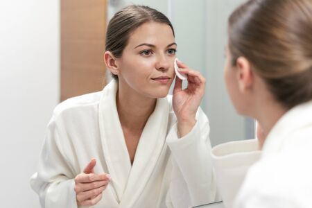 Beautiful young adult woman in white bathrobe holding cotton pad in hands, looking at mirror in bathroom and remove make up from face