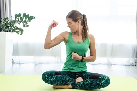 Young woman sitting on fitness mat with dumbbell in hand, training hard and looking at bicep muscle