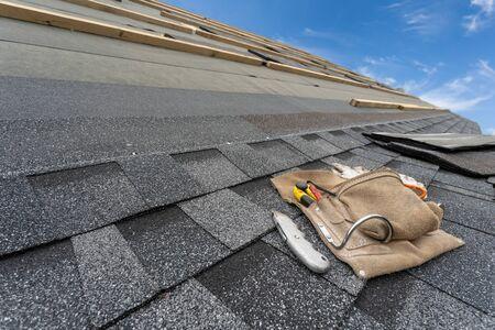 Primer plano y foto real del cinturón de herramientas con un cuchillo cortador especial sobre la instalación de tejas de asfalto o betún en la parte superior del nuevo techo en construcción de una casa o edificio residencial