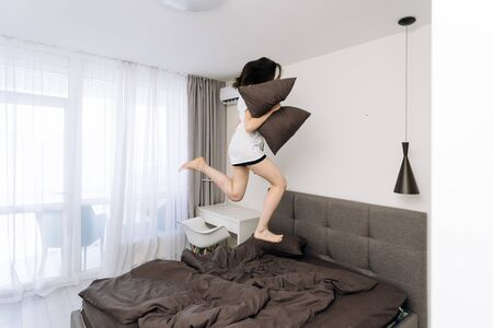 Happy and active young adult woman in casual t shirt jumping on bed in bedroom, holding pillow in hand and waking up at morning