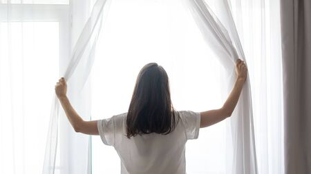 Rear view of young adult woman waking up at morning and standing near window with white tulle
