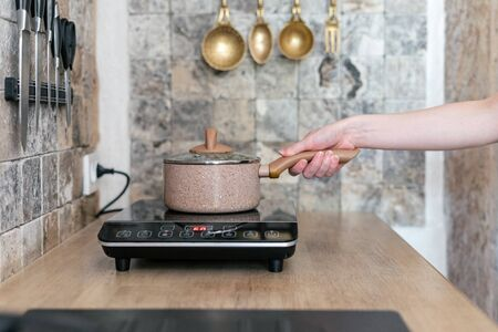 Cropped view of young adult woman holding pan over small electric stove. Girl cooking food in modern kitchen with wooden table, wall with marble tile and set of knives and cutlery on background
