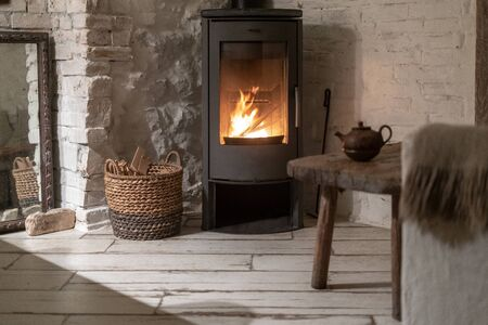 Wicker basket with firewood near fire chimney. Wood stove fireplace with metal body and glass door in comfort house with cozy interior in room