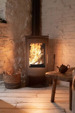 Vertical photo of wood stove fireplace with fire in metal body and glass door. Wicker basket in comfort house with cozy interior in warm room Stockfoto