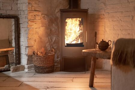 Table and teapot near wood stove fireplace in comfort house with cozy interior in room. Wicker basket with firewood near chimney with metal body and glass door Standard-Bild