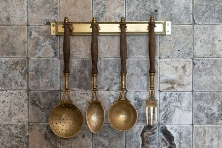 Element of interior in cozy home. Textured marble stone and square tile with set of vintage cooking cutlery on kitchen wall